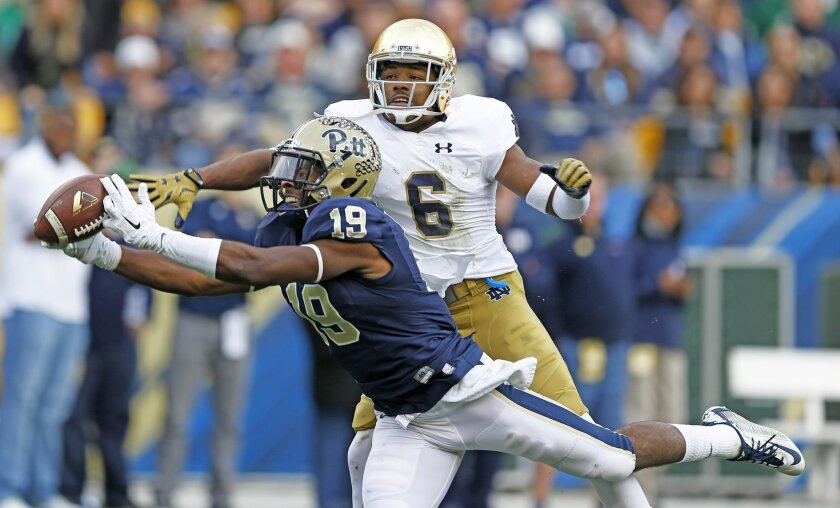 Pittsburgh wide receiver Dontez Ford (19) reaches to make a catch as Notre Dame cornerback KeiVarae Russell (6) defends in the second quarter of an NCAA football game, Saturday, Nov. 7, 2015 in Pittsburgh. The play was ruled a catch on the field, but was overturned as incomplete on replay.(AP Photo