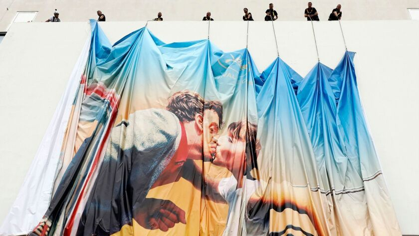 Workers install the official poster of the 71st Cannes Film Festival on the Palais des Festivals facade in Cannes, France.