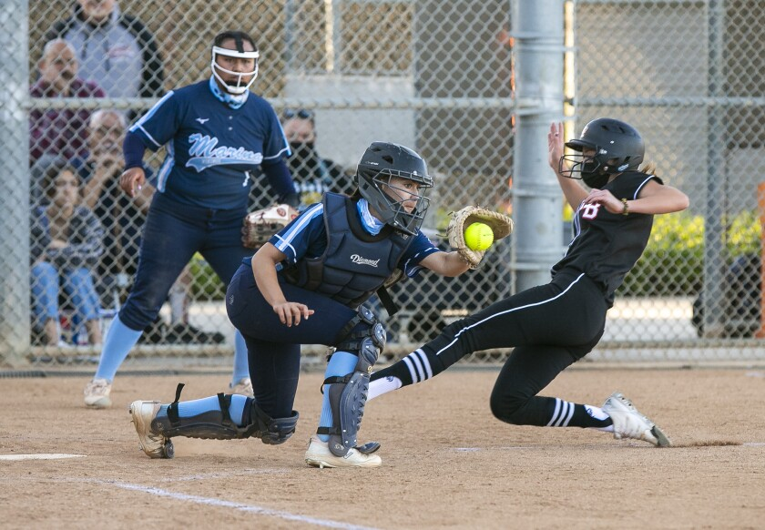 Huntington Beach's Emma Francisco beats the tag from Marina's Zoe King to score during a Surf League softball game.