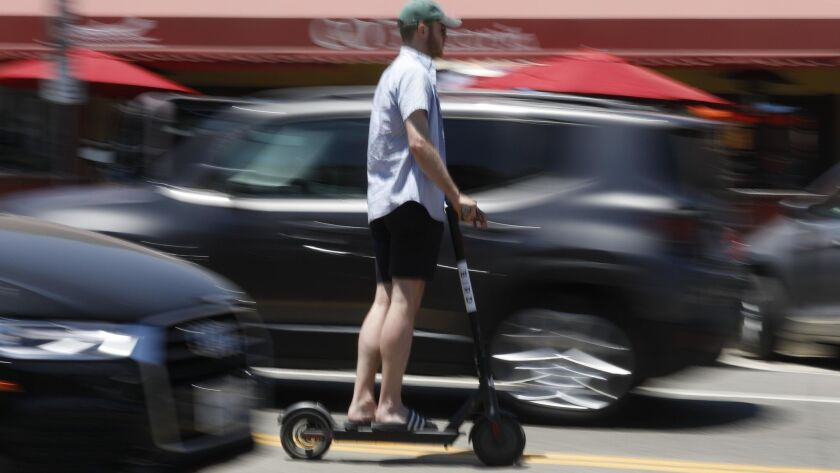 A helmetless Bird scooter user rides through traffic in Marina del Rey on July 5.