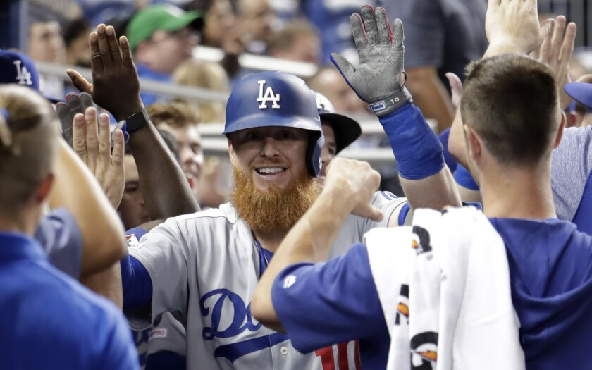 Justin Turner celebrates with his Dodgers teammates after hitting a two-run home run against the Miami Marlins on Tuesday.