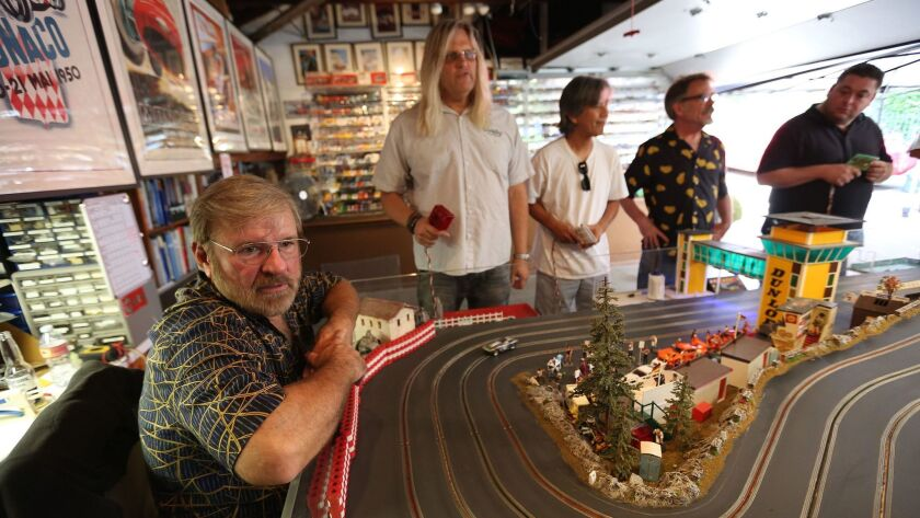 Michael Smalley, far left, watches fellow FarrOut Slot Car Club racers compete at a private track in Glendale.