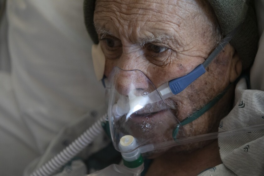 A man wears an oxygen mask connected to a tube while in bed.