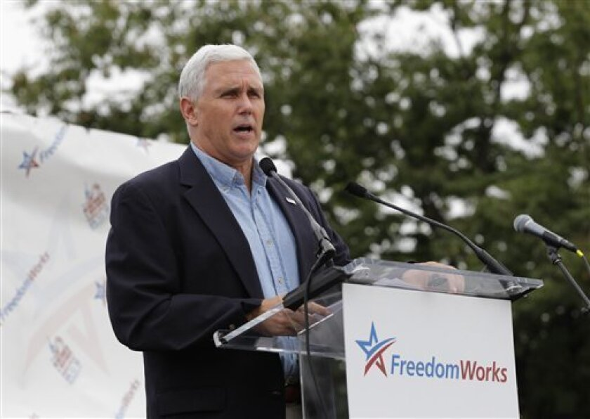 "Rep. Mike Pence, R-Ind., speaks to people gathered at the Capitol for a ""Remember in November"" rally to express opposition to government spending, particularly bailouts and economic policies backed by President Obama and Democrats in Congress, in Washington, Sunday, Sept. 12, 2010.  (AP Photo/J. Sc"