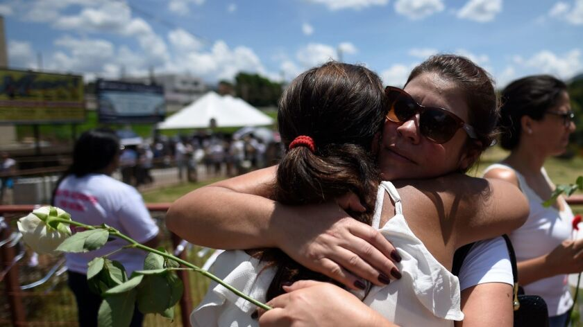 People mourn during a tribute to the victims one month after the collapse of a dam at an iron-ore mine near the town of Brumadinho, Brazil, on Feb. 25,