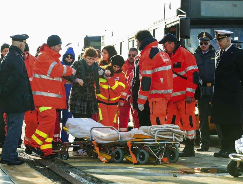 An injured passenger is being eased to a stretcher as she and some 40 of the survivors of the Norman Atlantic ferry fire, finally stepped ashore, in the port of Taranto, Italy, Wednesday, Dec. 31, 2014. They arrived by one of the cargo ships that took aboard passengers from the flaming, smoke-shrou