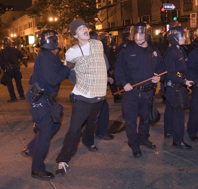 Un manifestante es detenido por la policía en el centro de Oakland después de que un jurado de Los Ángeles declarase culpable al agente de tránsito Johannes Mehserle de homicidio involuntario al disparar contra un joven afroamericano en una estación de tren de Oakland, California, Estados Unidos, el jueves, 8 de julio de 2010. EFE/Peter Da Silva/Archivo
