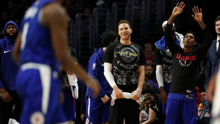 Clippers forward Blake Griffin, middle, and guard Lou Williams, right, cheer on the team in the final moments of the Clippers' win against the Sacramento Kings on Saturday at Staples Center.