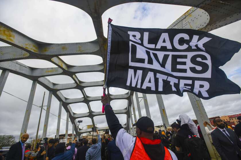 FILE - In this March 3, 2019, file photo, Black Lives Matter demonstrator waves a flag on the Edmund Pettus Bridge during the Bloody Sunday commemoration in Selma, Ala. Majorities of Americans across racial lines say white people are treated more fairly than black people by the police, according to a new poll from The Associated Press-NORC Center for Public Affairs Research. The dynamic has played out in the wake of the Black Lives Matter movement, which began in 2014 with the fatal shooting of unarmed 18-year-old Michael Brown by white, former Ferguson, Mo., police officer Darren Wilson. (AP Photo/Julie Bennett, File)