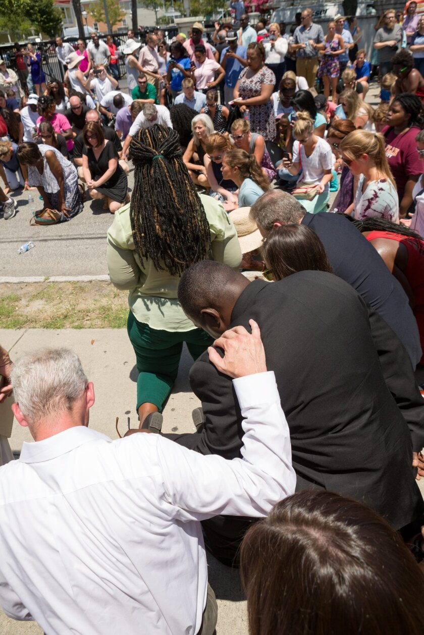 Charleston residents bow in prayer during a vigil for the nine victims of a mass shooting in the Emanuel African Methodist Episcopalian Church in Charleston, S.C. Police arrested a lone gunman in what they have categorized a hate crime.