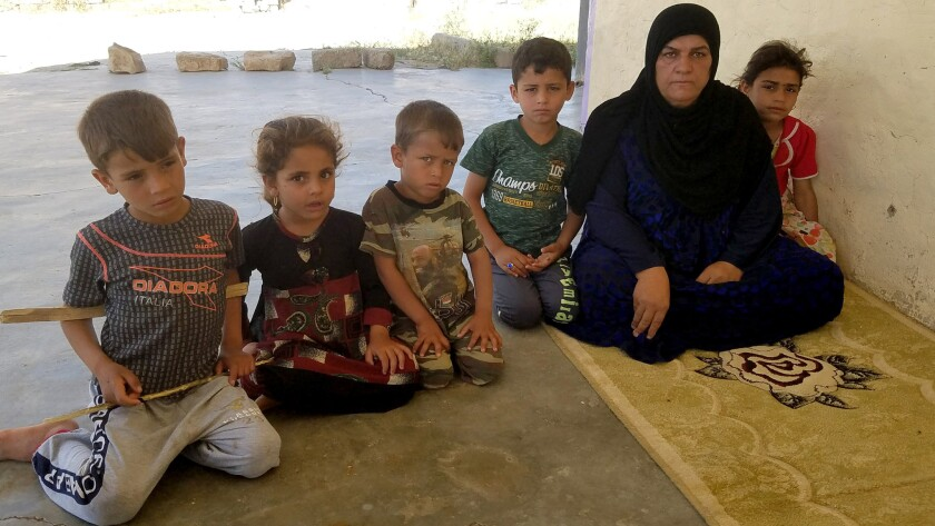 Khalida Yasin Hamid, 50, is flanked by grandchildren Yasin, 9, and Hameen, 6, whose father was kill