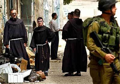 Monks stand in the alley off Manger Square.