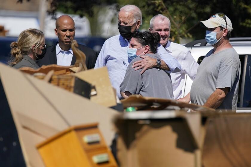 President Joe Biden hugs a person as he tours Manville, N.J.