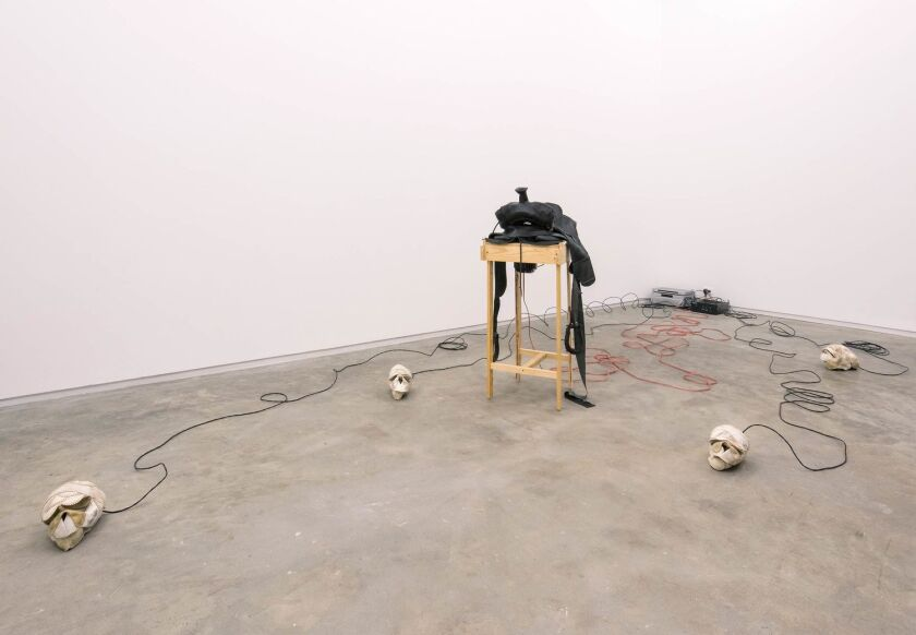 A gallery features skulls made from worn softballs connected by wires to a wooden plinth