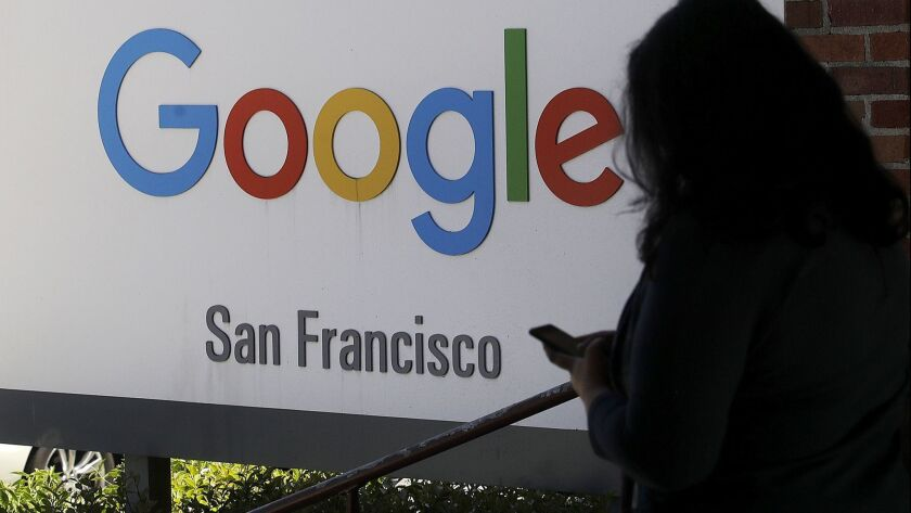 FILE - In this May 1, 2019, file photo, a woman walks past a Google sign in San Francisco. Google is