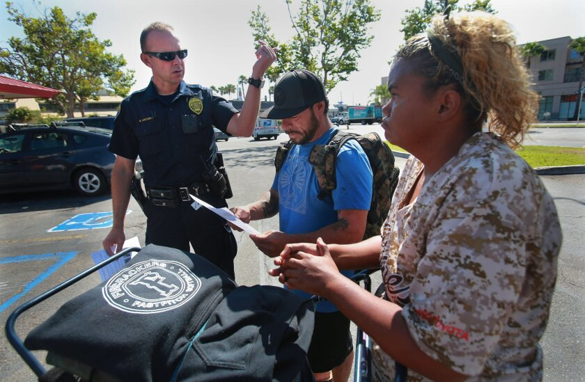 San Diego Homeless Outreach Team officer Brian Lucchesi canvasses several areas in the Midway and Sports Arena Blvd. area Wednesday, July 6, 2016, stopping to talk with people like Robert and Krista, two homeless people who stay in the area. The couple hadn't heard about the recent assaults on the