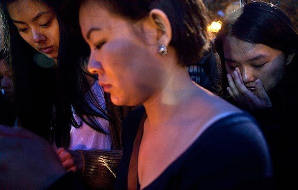 Shannon Cheng, center, and Nan Lin, right, mourn at a candlelight vigil Wednesday night. On Wednesday morning, two students were shot to death about a mile from campus.