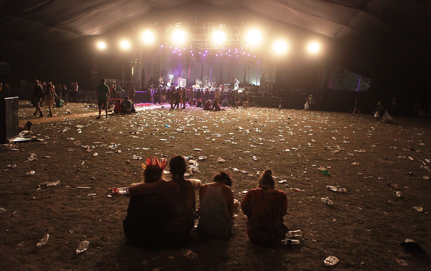 Fans sit on a trash-strewn lawn in front of the Gobi stage between shows on the second day of the Coachella Valley Music and Arts Festival in Indio.