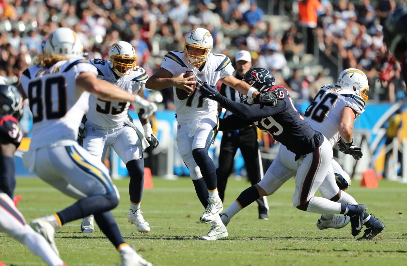 Chargers quarterback Philip Rivers ends up fumbling the ball while trying to evade a sack.