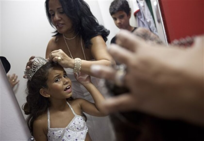 Monica Lira puts a crown on her seven-year-old daughter Julia before a rehearsal by the Viradouro samba school in Rio de Janeiro, late Wednesday, Feb. 3, 2010. The tiny dancer will be at the helm of the Viradouro samba school's parade at the upcoming Rio carnival. The Viradouro samba school has been known in the past for having local superstar actresses at the front of their shows. (AP Photo/Felipe Dana)