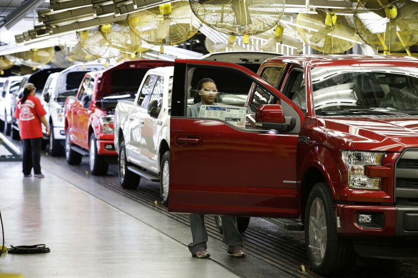 Ford workers inspect 2015 aluminum-alloy body Ford F-150 trucks at the company's plant in Claycomo, Mo., in March.