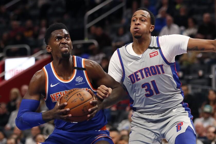 New York Knicks forward Bobby Portis, left, looks towards the basket as Detroit Pistons forward John Henson (31) defense during the first half of an NBA basketball game, Saturday, Feb. 8, 2020, in Detroit. (AP Photo/Carlos Osorio)