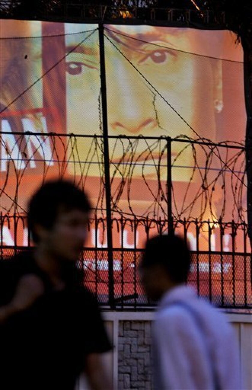 Pwoplw walk by a projected image of Myanmar opposition leader Aung San Suu Kyi on a screen put up inside the British Embassy compound in Jakarta, Indonesia, Thursday, July 2, 2009. British embassy in Jakarta displayed the image of the imprisoned pro-democracy leader Thursday to join calls from different parts of the globe for the military government of Myanmar to release Suu Kyi and other political prisoners in Myanmar. (AP Photo/Dita Alangkara)