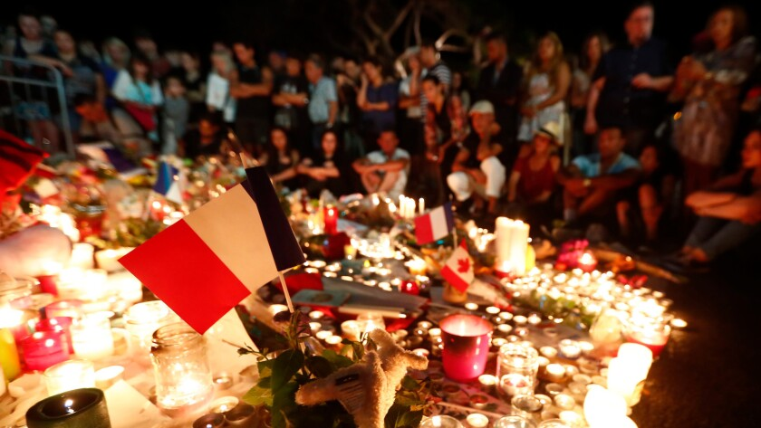 People gather at a memorial on the Promenade des Anglais in Nice, France, where a truck crashed into the crowd during Bastille Day celebrations.