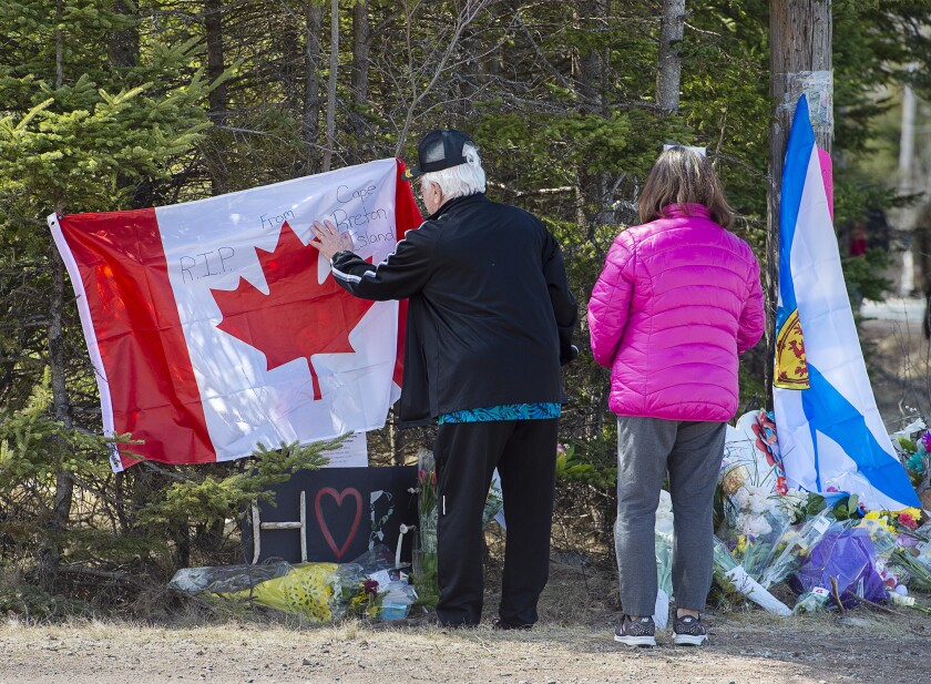 A couple visits a makeshift memorial for victims of a shooting rampage.