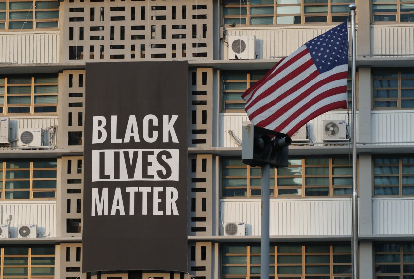 In this June 14, 2020 photo, U.S. flag flutters next to a giant Black Lives Matter banner at the U.S. Embassy in Seoul, South Korea. The banner has been removed from the U.S. Embassy building in South Korea's capital three days after it was raised there in solidarity with protesters back home.(AP Photo/Lee Jin-man)