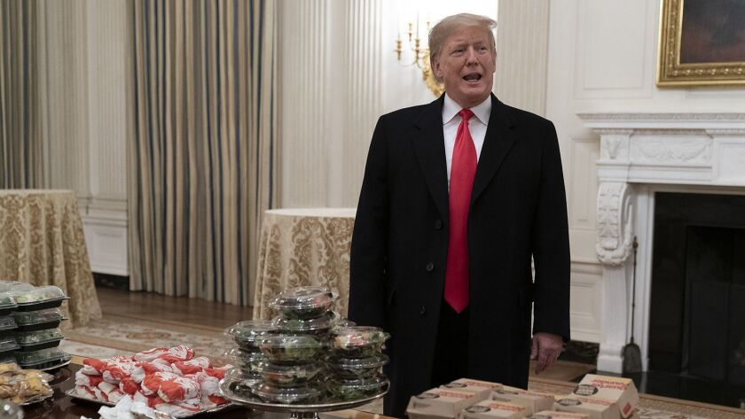 President Trump presents fast food to be served to the Clemson Tigers football team to celebrate their national championship. He now weighs 243 pounds, up from 236 pounds in September 2016.