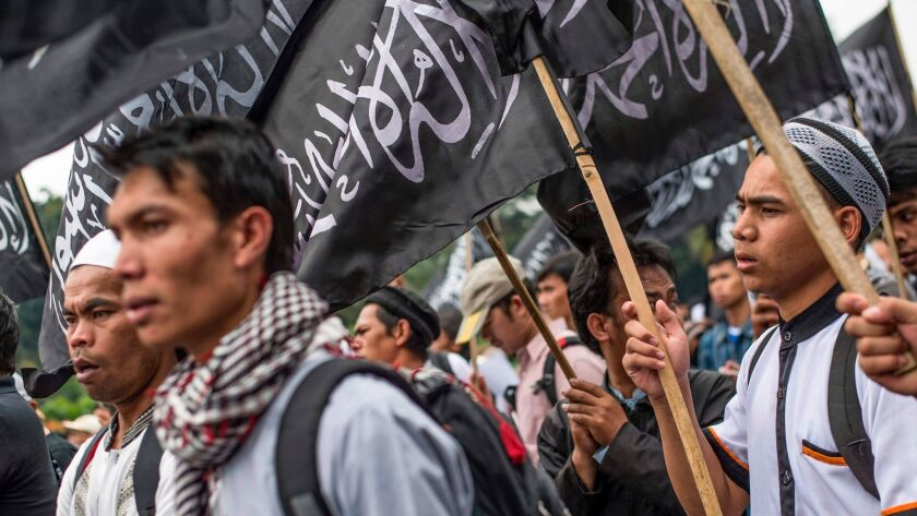 Indonesian Muslims wave Hizbut Tahrir's flag during a protest July 18 in Jakarta against a decree allowinag the country to ban groups that oppose its official state ideology.