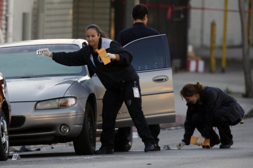 LAPD officers investigate an officer-involved shooting on Pico Boulevard just east of Bonnie Brae Street.