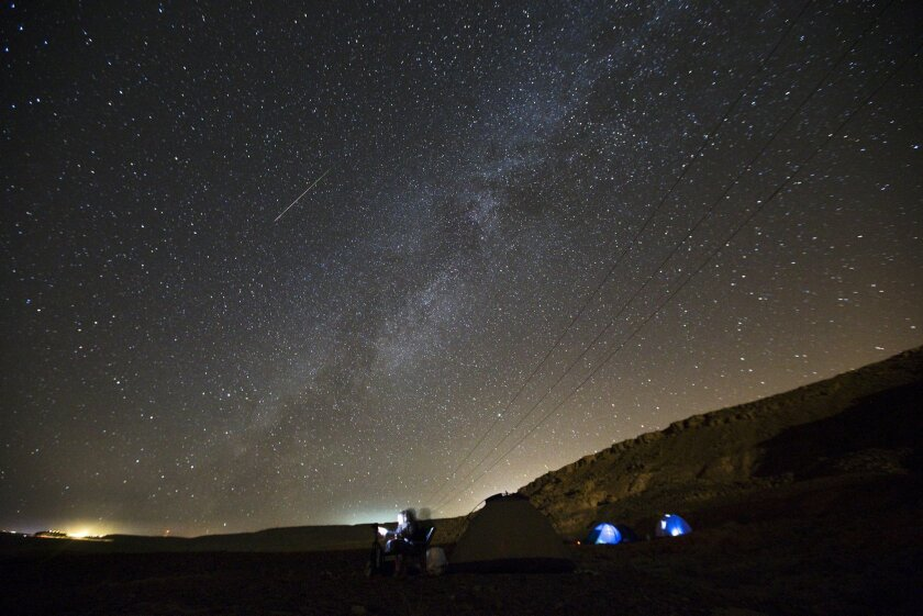 A meteor streaks across the sky in the early morning as people watching during the Perseid meteor shower in Ramon Carter near the town of Mitzpe Ramon, southern Israel.