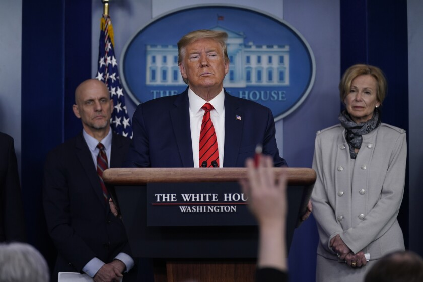 President Trump takes questions during a news briefing Thursday, flanked by Dr. Stephen Hahn, commissioner of the FDA, and Dr. Deborah Birx, White House coronavirus response coordinator.