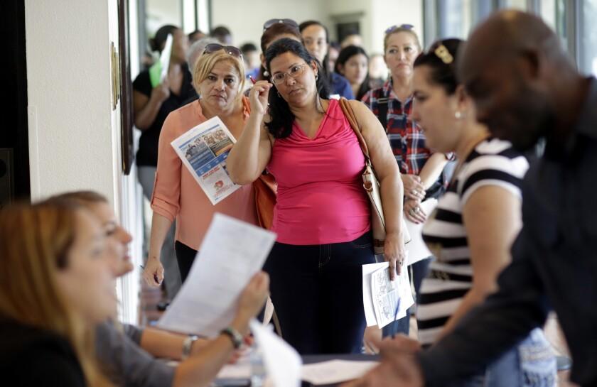 En esta foto del 19 de julio de 2016, Reina Borges, izquierda, presenta solicitud de empleo en una feria laboral en Miami Lakes, Florida. La economía creó 225.000 empleos en julio y la tasa de desempleo se mantuvo en 4,5%, informó el gobierno el viernes 5 de agosto de 2016. (AP Foto/Lynne Sladky)