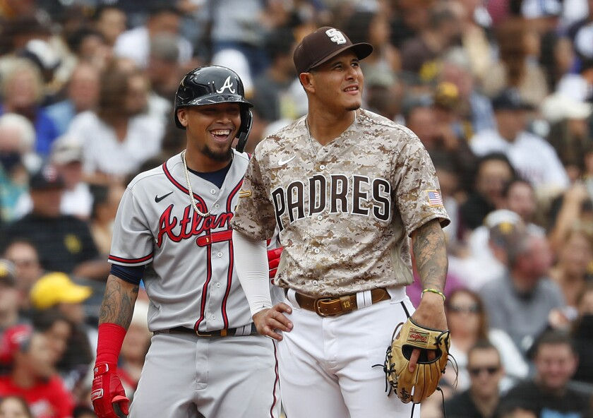 Manny Machado and the Atlanta Braves' Eddie Rosario smile after Rosario hit a RBI triple in the sixth inning on Sunday.