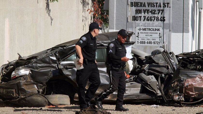 Police officers walk by a mangled vehicle that was clipped by a Metrolink train near near the intersection of San Fernando Boulevard and Buena Vista Street. (Tim Berger / Burbank Leader)