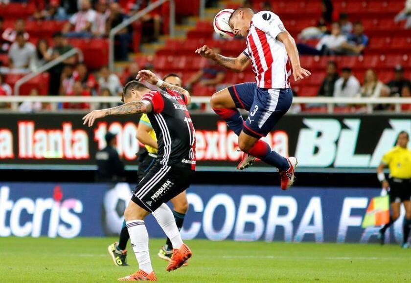 Carlos Salcido (d) de Chivas disputa el balón contra Milton Caraglio (i) de Atlas. EFE/Archivo