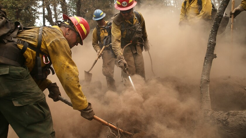 Firefighters mop up hot spots in an area burned by the King fire on Sept. 19 near Pollock Pines, Calif. The King fire is threatening more than 12,000 homes in the forested area about an hour east of Sacramento.