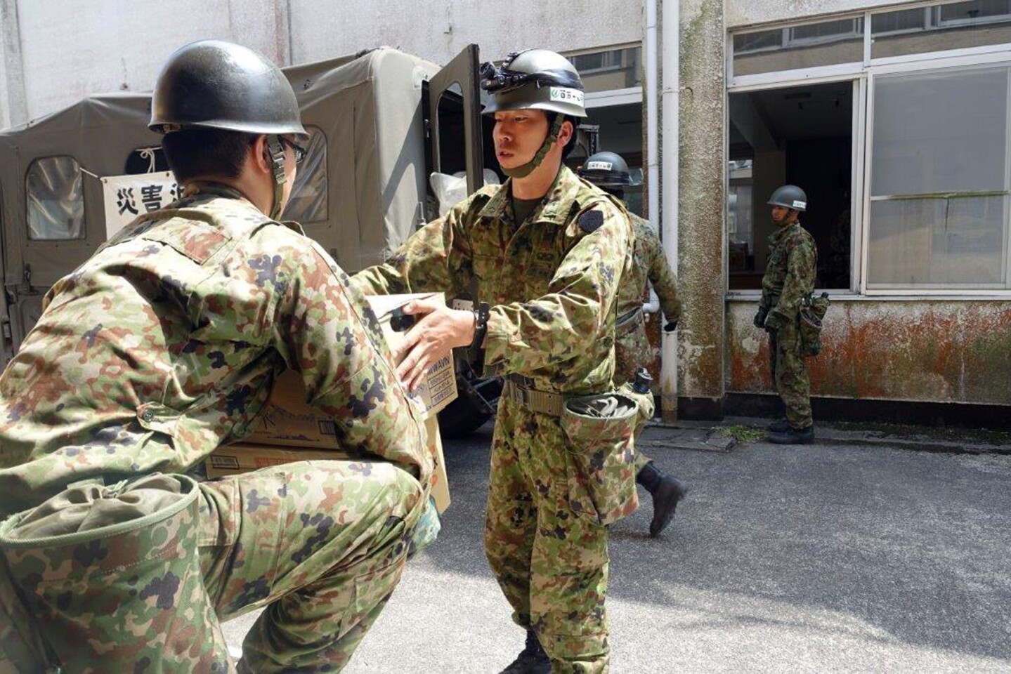 Troops bring in supplies to set up a new shelter in Minamiaso, Kumamoto prefecture, Japan Tuesday, April 19, 2016. Evacuees at a gymnasium were moving to another shelter Tuesday, a nearby former elementary school, because some expressed fears after the strong aftershock, because the gym stands on the hill.