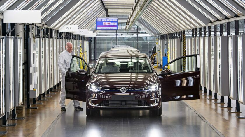 A worker performs a final check on an e-Golf electric car at a Volkswagen factory in Dresden, Germany.