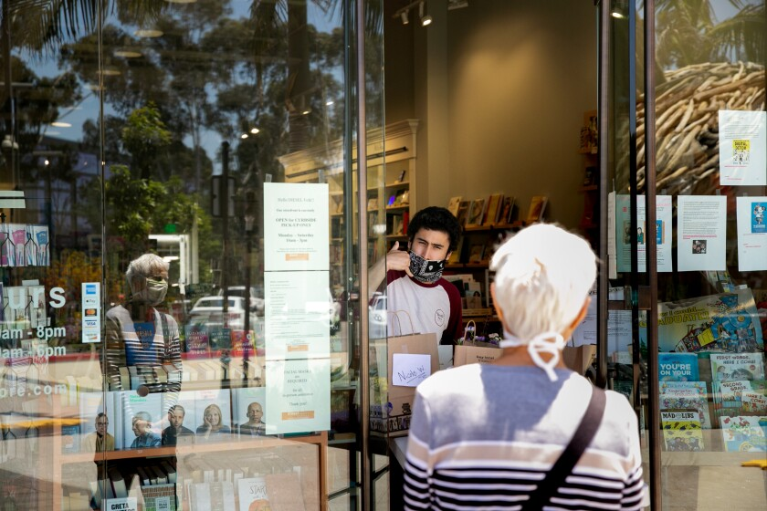 Freddy Gomez, an employee at Diesel, A Bookstore, tells customer Kathy Mortimer she needs to call ahead to pay before picking up a gift card in the Del Mar Highlands shopping center on May 8.