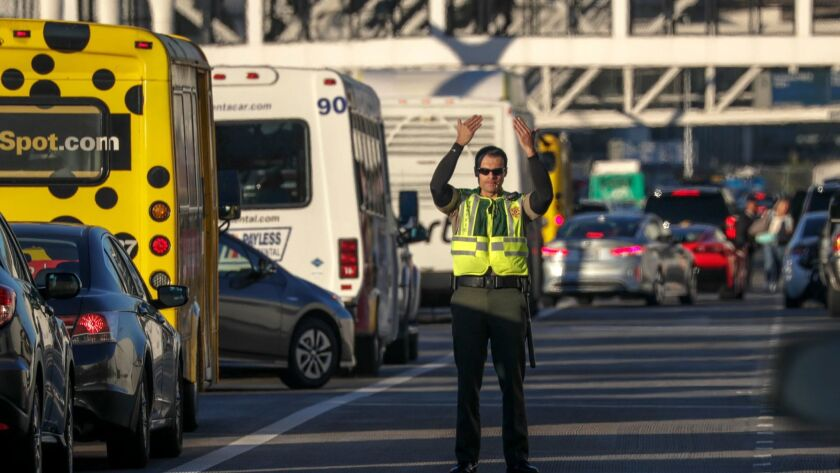 A Los Angeles airport police officer directs traffic at Los Angeles International Airport on the day before Thanksgiving last year. A study ranked LAX near the bottom when it comes to transit options, drive time and cost of getting to the airport.