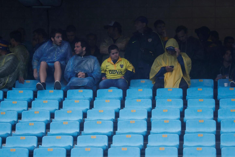 """ARG01. BUENOS AIRES (ARGENTINA), 10/11/2018.- Hinchas de Boca Juniors permanecen bajo la lluvia al interior del estadio La Bombonera hoy, s?bado 10 de noviembre de 2018, en Buenos Aires (Argentina). El partido de ida de la final de la Copa Libertadores entre Boca Juniors y River Plate, que deb?a jugarse este s?bado a las 17.00 horas (20.000 GMT) en la Bombonera, se suspendi? por la fuerte tormenta que azota a la ciudad de Buenos Aires, inform? el presidente del Xeneizo, Daniel Angelici. """"S?, se suspendi?"""", dijo Angelici al canal Fox Sports. Se cree que se juegue el domingo a las 16.00 horas (19.00 GMT). EFE/Juan Ignacio Roncoroni ** Usable by HOY and SD Only **"""
