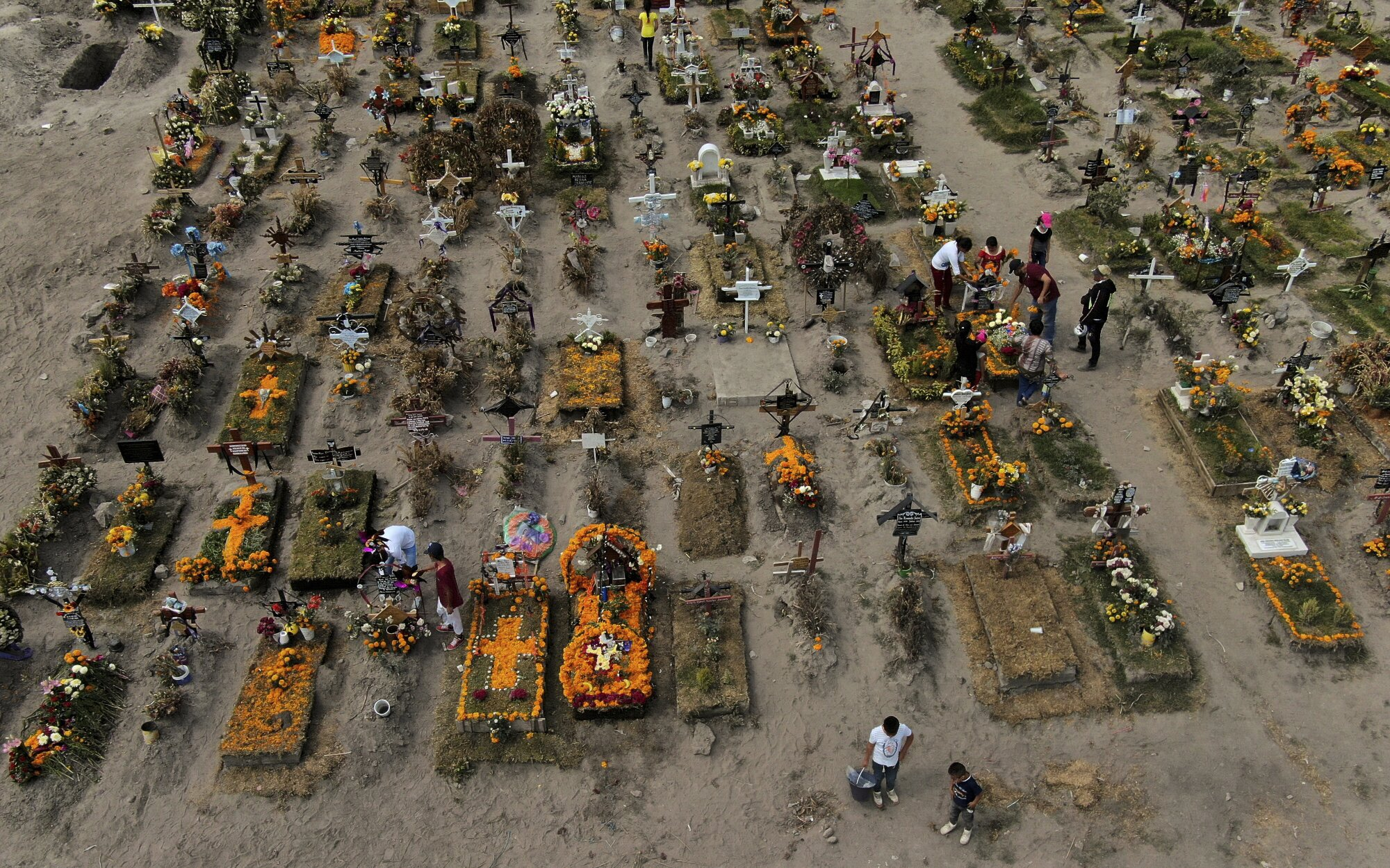 An aerial view of rows of graves adorned with flowers in a dirt graveyard