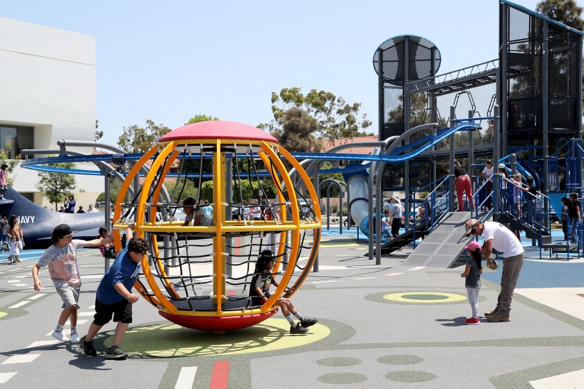 Children and adults enjoy the new playground at Lions Park in Costa Mesa, July 17, 2021.