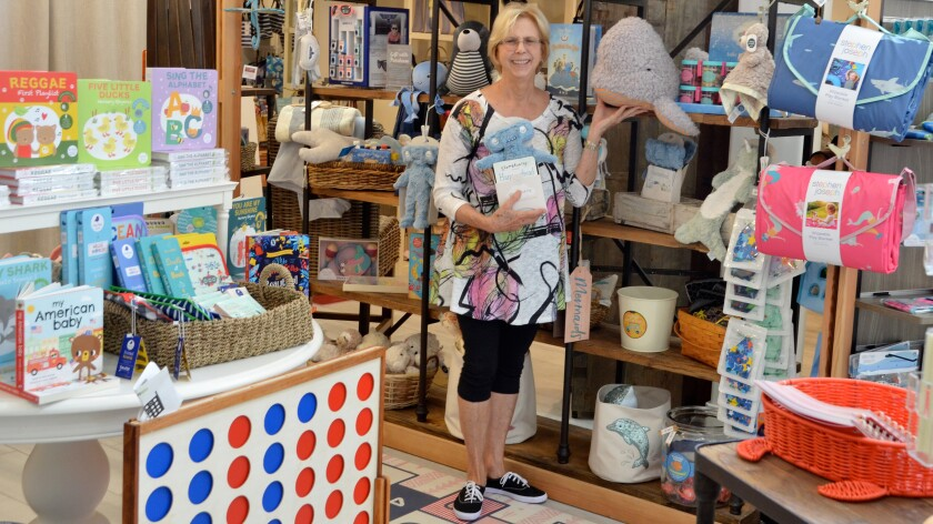 Susan Dawson, store manager of Sur La Mer Coastal Goods, shows items for sale in the kids' section.