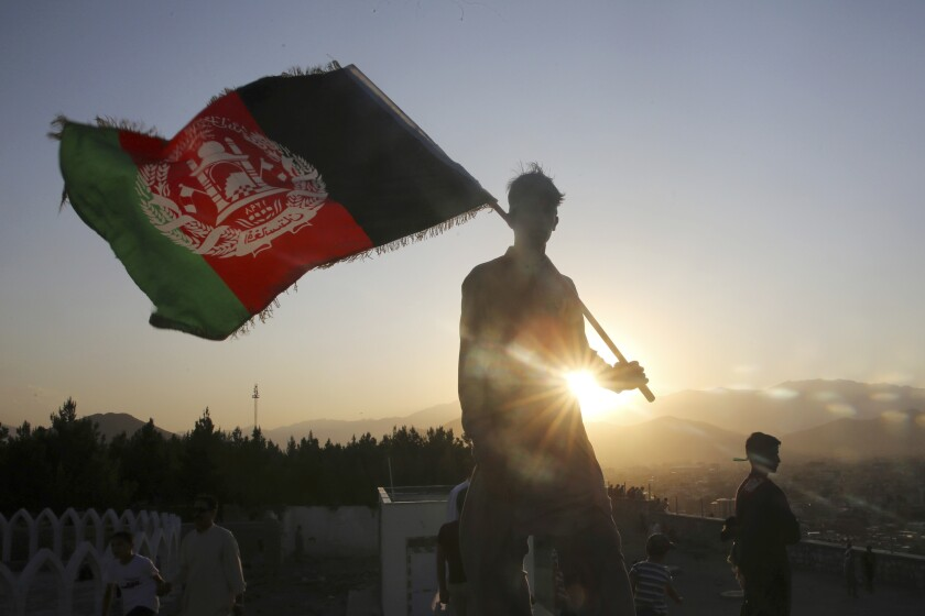 "FILE - In this Aug. 19, 2019, file photo, a man waves an Afghan national flag during Independence Day celebrations in Kabul, Afghanistan. Washington's watchdog warns, Thursday, June 25, 2020, that ""systemic"" corruption within the Afghan government is weakening its bargaining position in future peace negotiations with the Taliban, even as the insurgent group's political spokesman says the group was ready with its agenda for talks. (AP Photo/Rafiq Maqbool, File)"