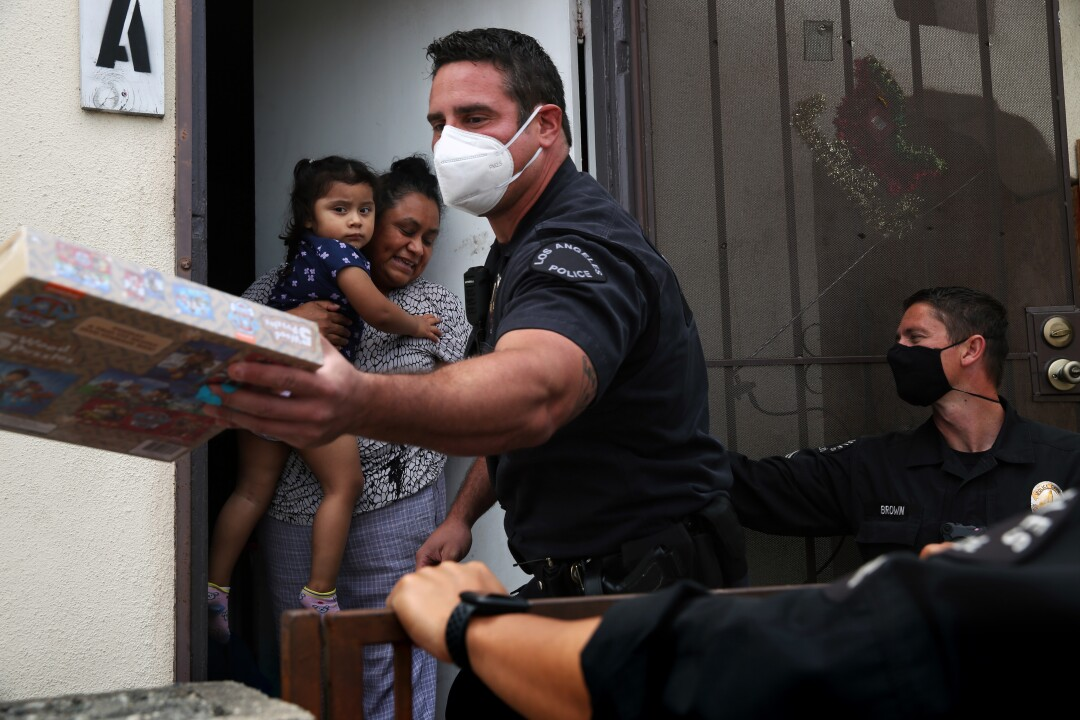 Los Angeles Police Officer Nick Ferara, center, with Officer Dan Brown, right, gives Victoria Taboada a game for her 3-year-old daughter in San Pedro